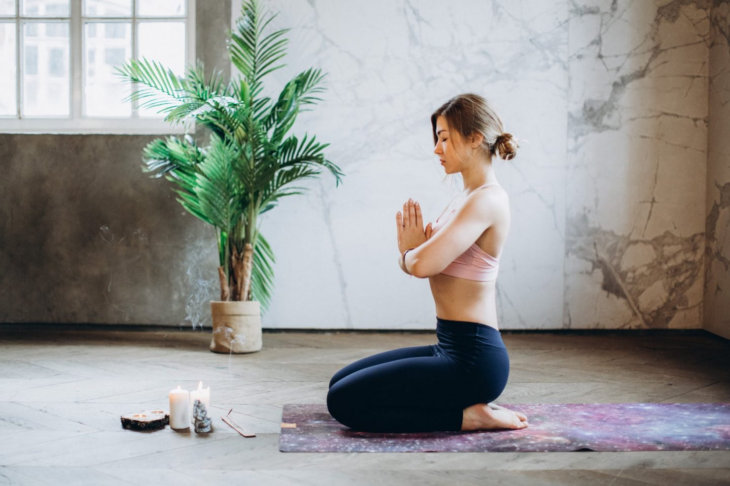 woman meditating with candles and incense