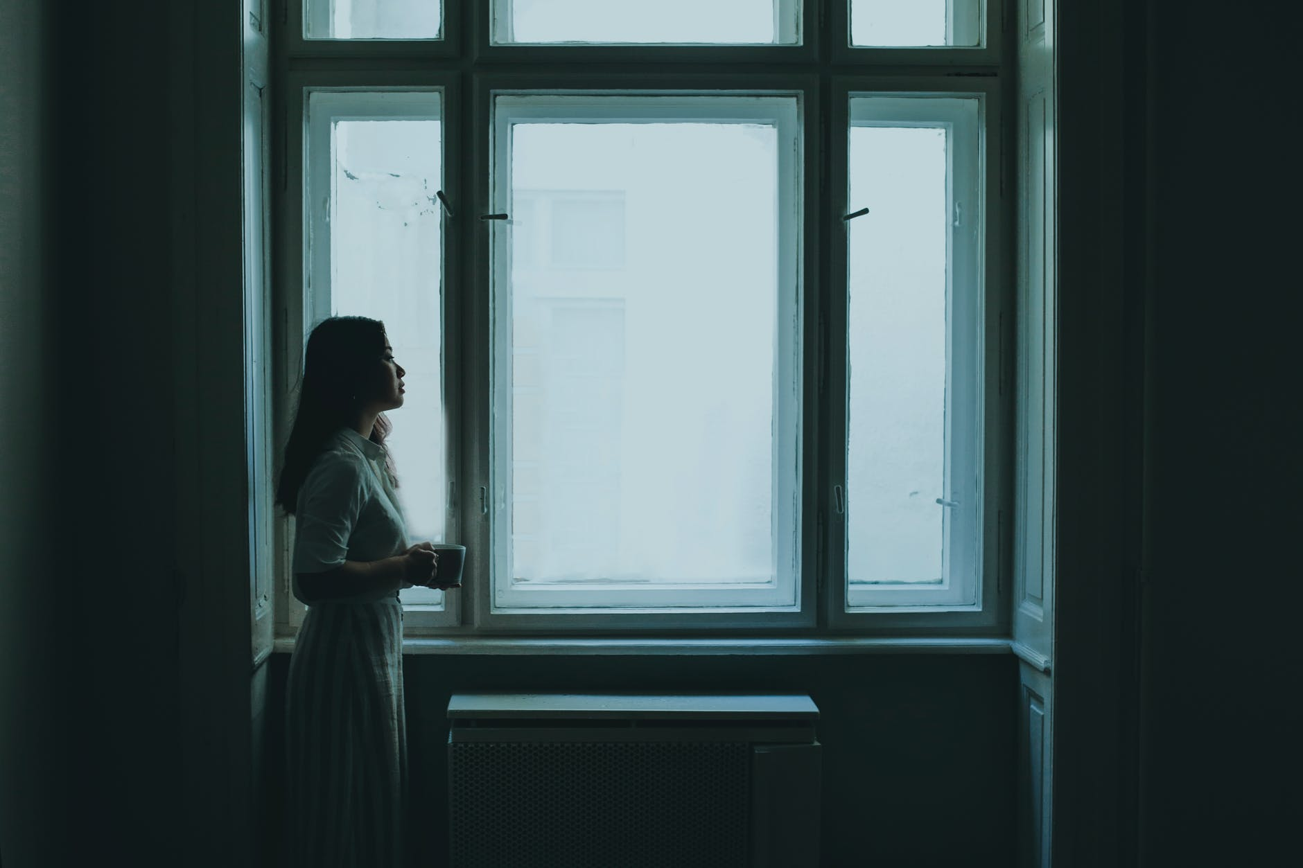 thoughtful young woman drinking coffee near window on gloomy day