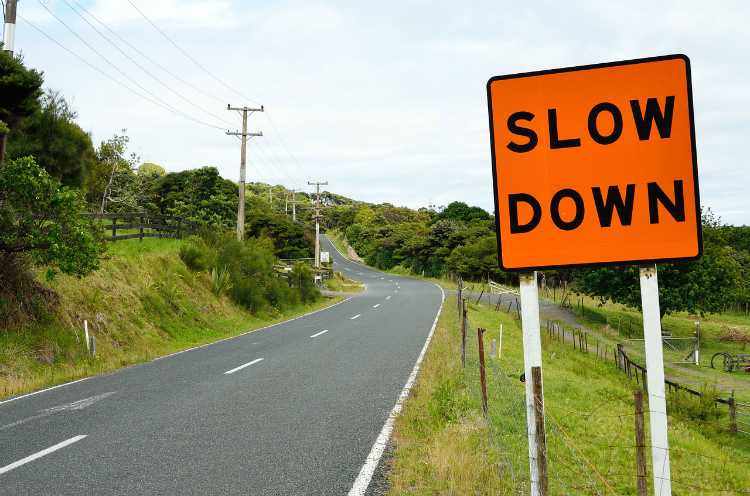 slow down road sign