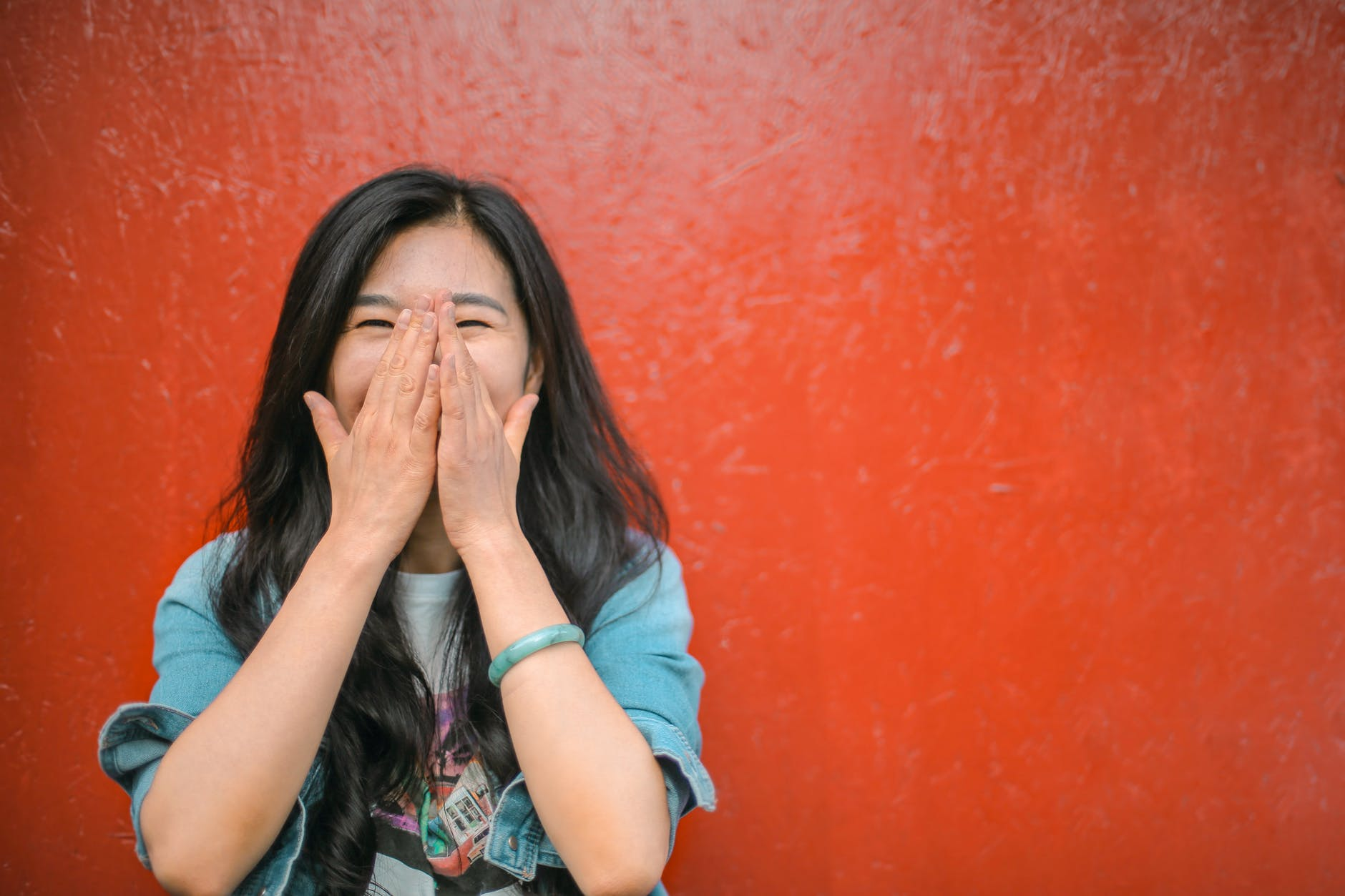 cheerful ethnic woman against vivid red painted wall